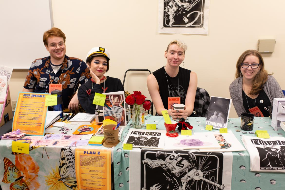 4 students behind a table selling their work at a comic book convention