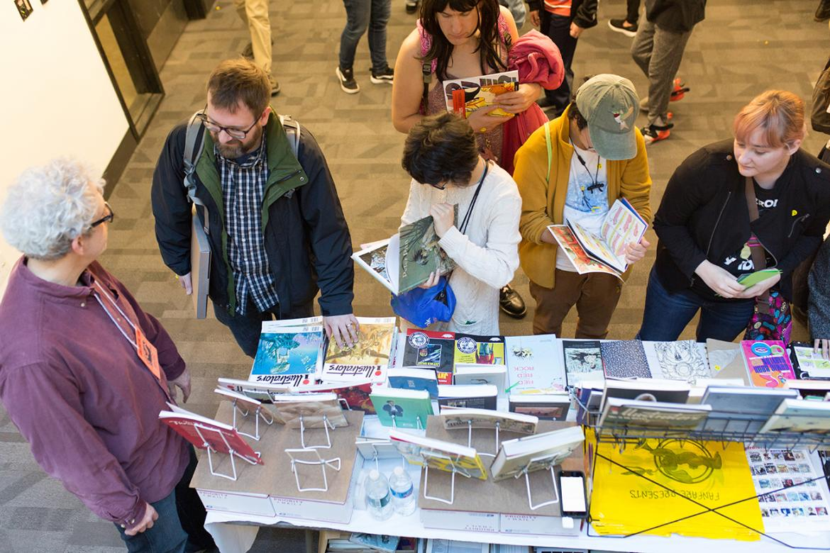 Guests browsing and looking at artwork and comic books at convention at Lesley
