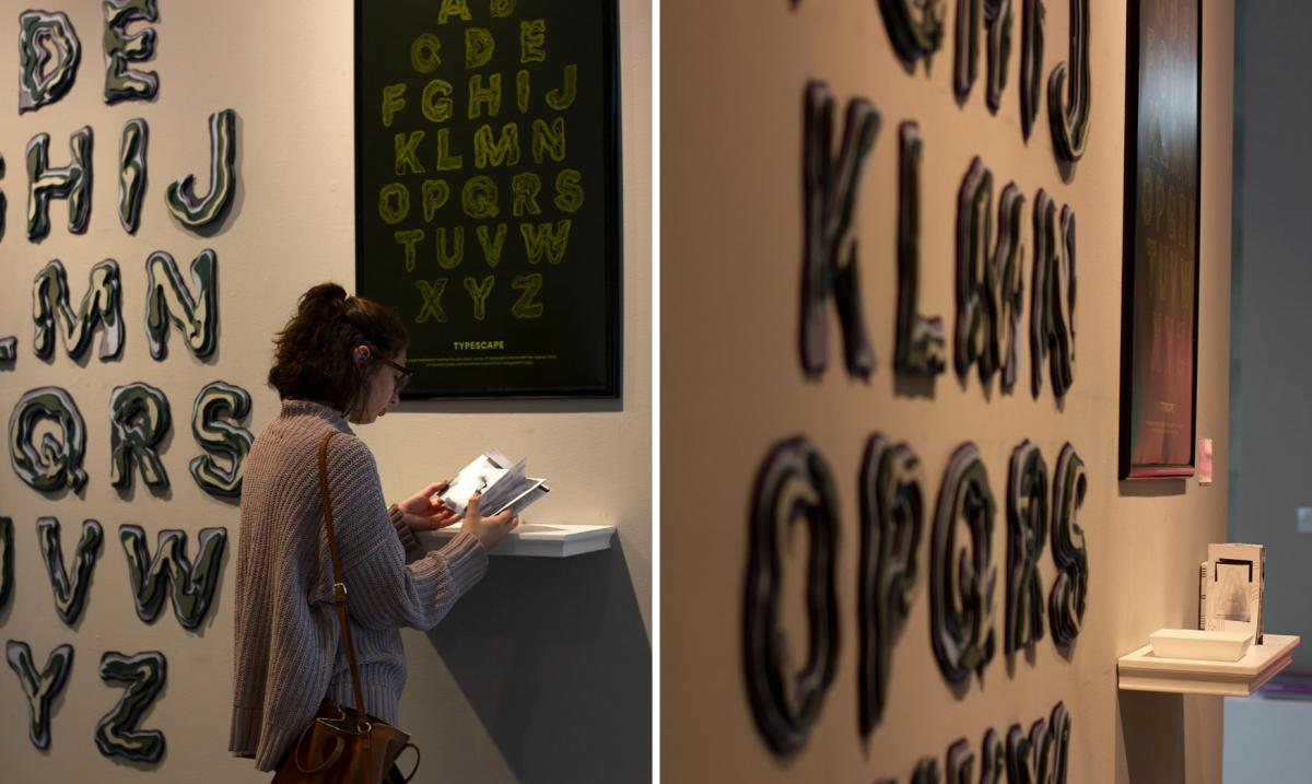 woman looks at art installation with wooden block letters on the wall