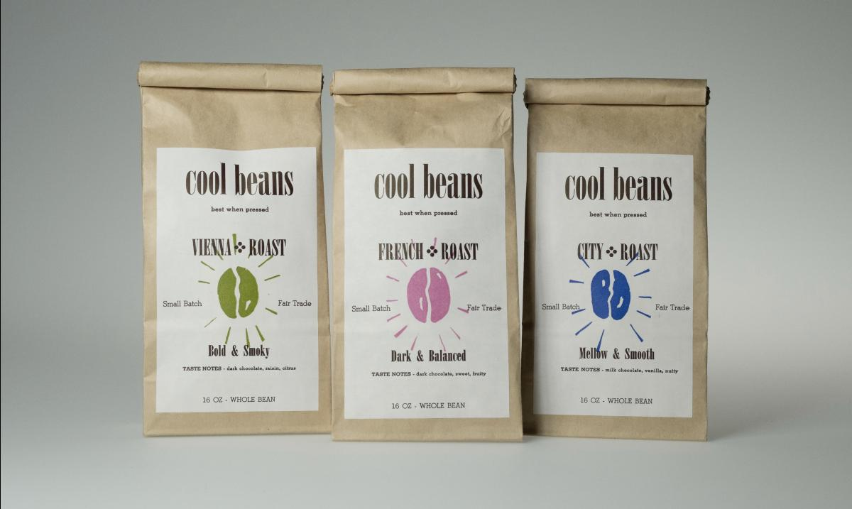 "three bags of coffee grounds in brown bags with ""Cool Beans"" white label on them."