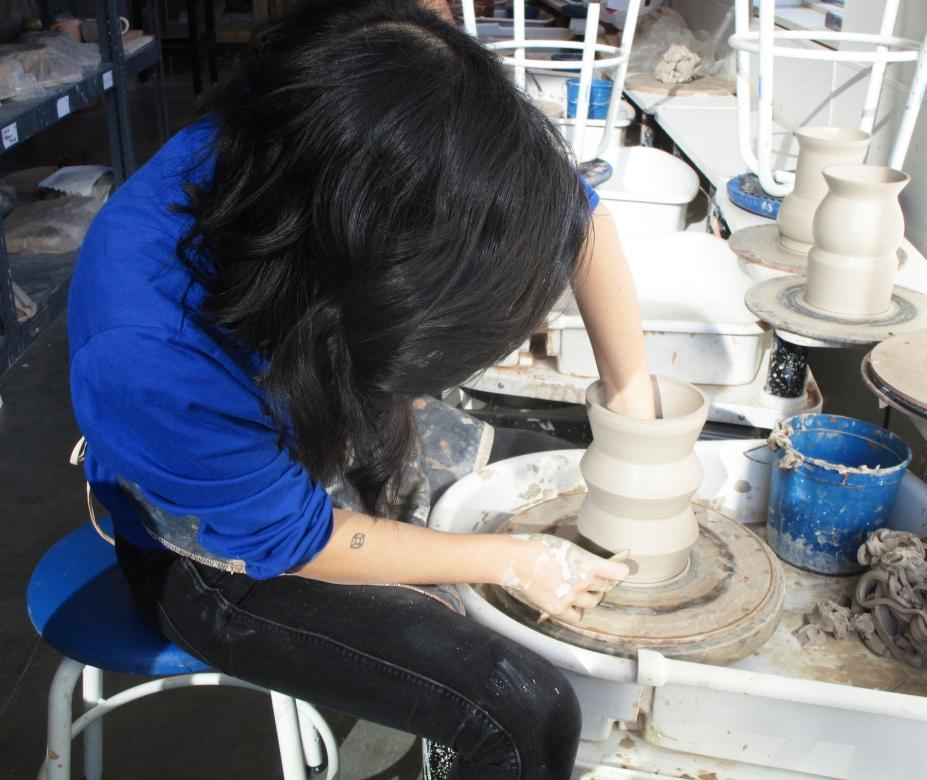 students works at a potter's wheel making a clay vase