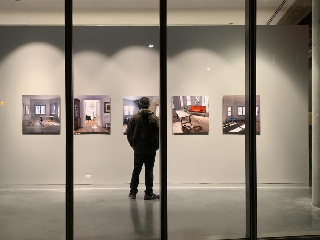 man in gallery looking at art hanging on wall