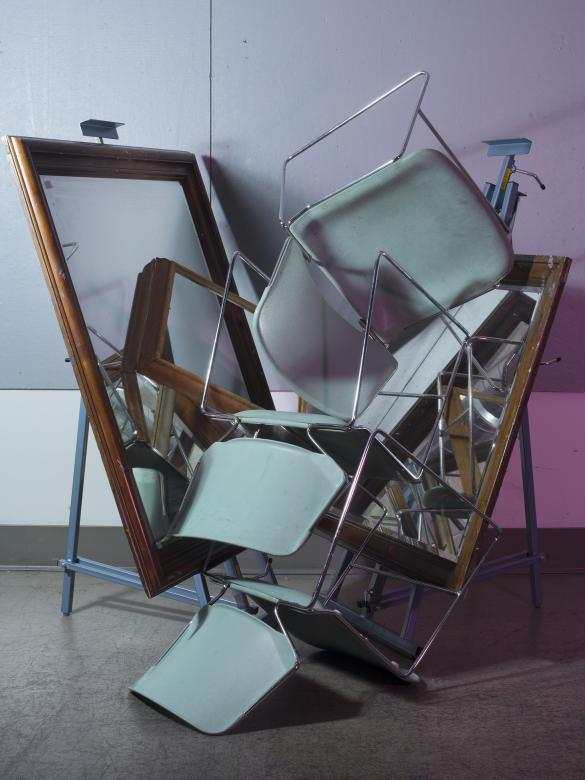 Photograph of pale blue classroom chairs piled together with large mirrors on either side of pile. Purple light is reflected in the background