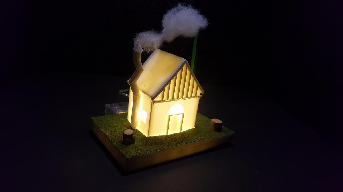 tiny house that was printed on a 3D printer. A light is on and smoke is coming out of the chimney.