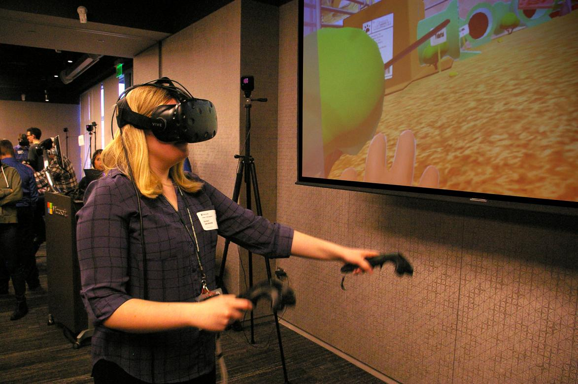 student tries out virtual reality design, wearing a headset and using hand cotrollers
