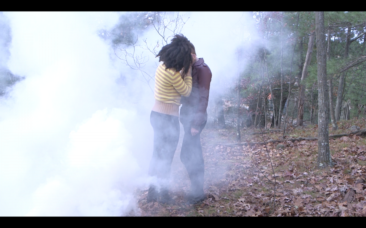 Two young people kiss in a cloud of smoke in the woods.
