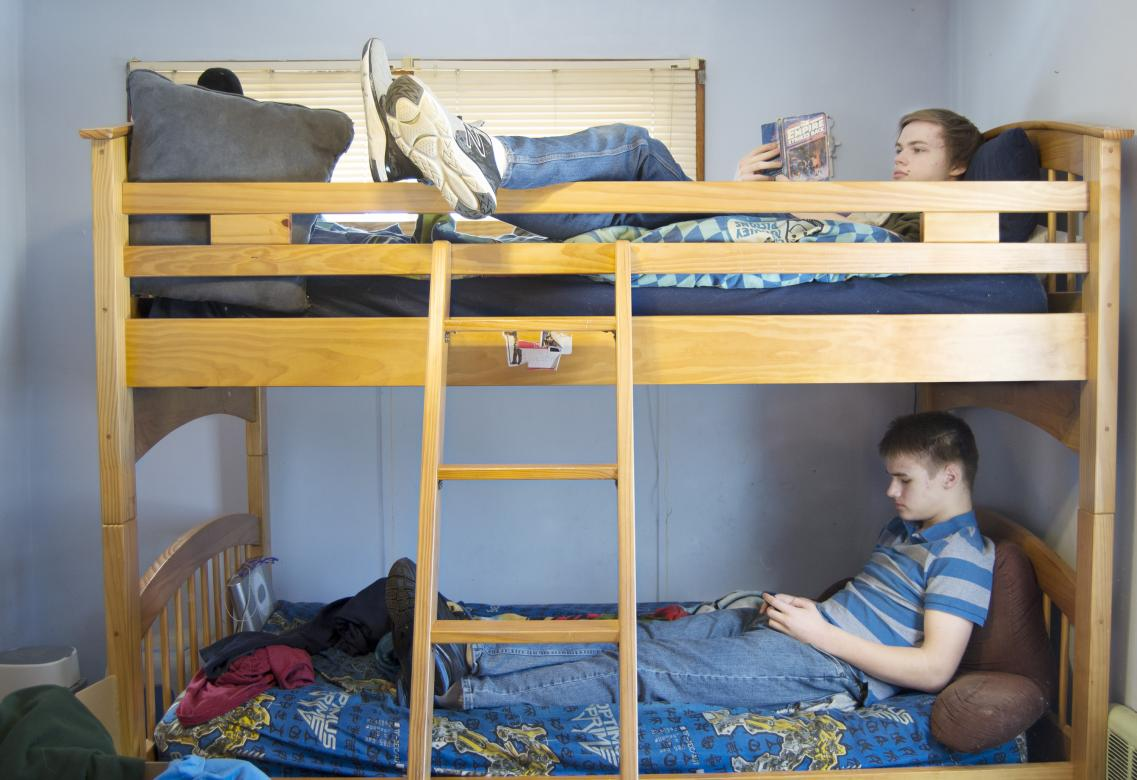 two young boys sit on bunk beds