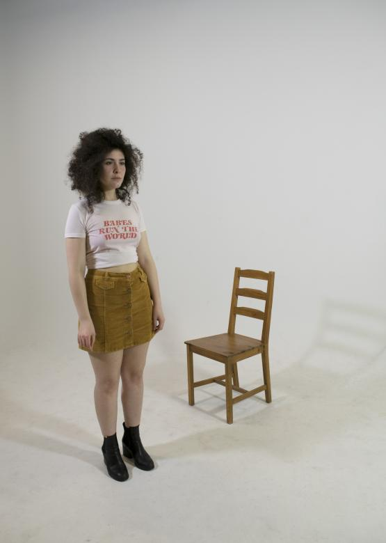 young person stands on white backdrop infront of a wooden chair