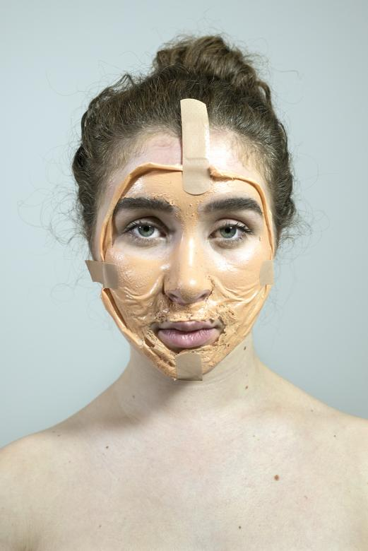young person sits with thick foundation on her face with bandaids around her head