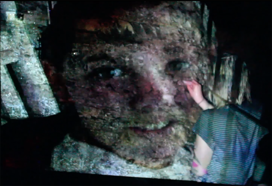 video still of person writing on a projected image of a child's face