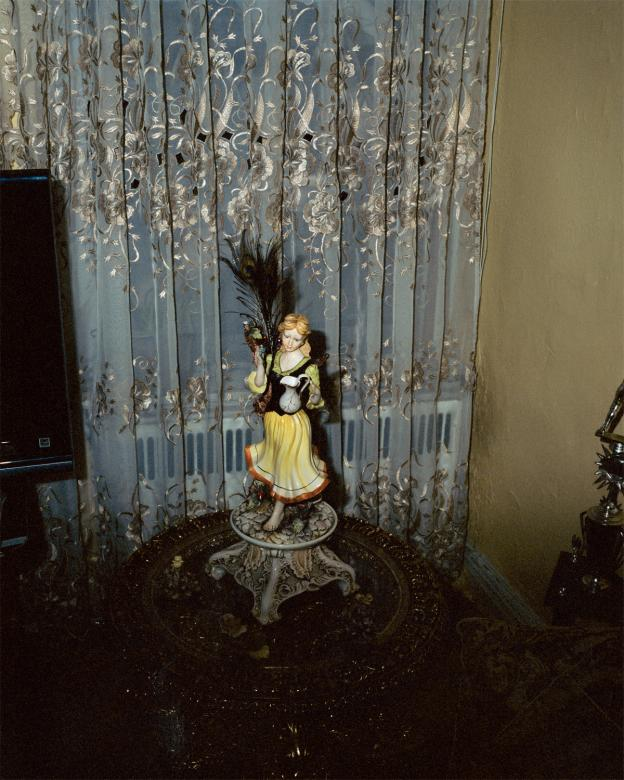 Photograph of ceramic figure on a flashy table in front of white and gold curtains