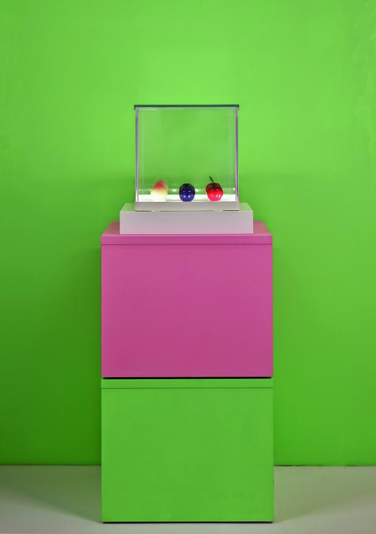 Large green and pink stacking blocks with plastic fruit displayed under glass on top