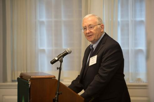 Donald Perrin speaks at a podium in Alumni Hall