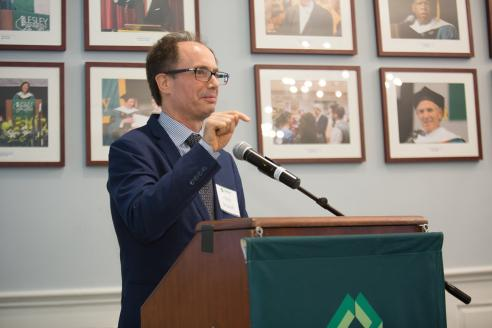 Hans Strauch speaks at a podium in Alumni Hall