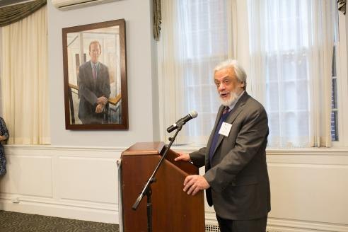Tony Apesos speaks at a podium in Alumni Hall with his painting of Joe Moore visible in the background.