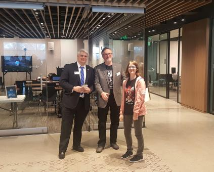 student Jess Brown stands with two judges at the Microsoft Education Center Office