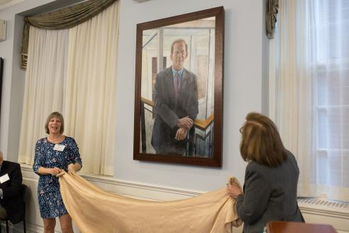 Beth Chiquoine and Deborah Raizes pull down a cloth to unveil the portrait.