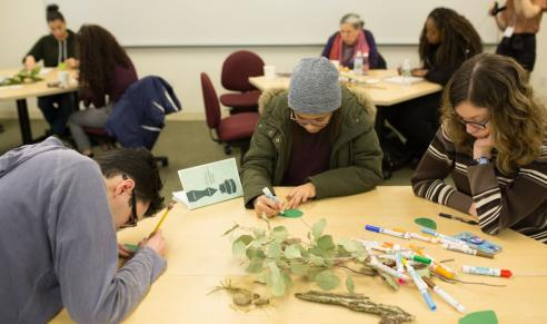Participants sit at tables working with markers and natural materials