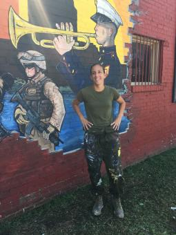 McKelvey stands in gront of a mural she painted on a wall for Marine Week Detroit in 2017.