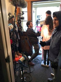 a film crew prepare for a shot in a small doorway