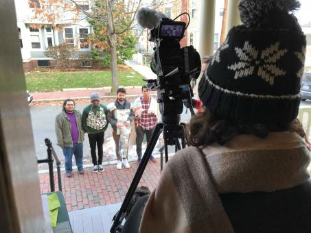 a picture of someone behind a video camera, filming four guys on a sidewalk wearing homemade armor.