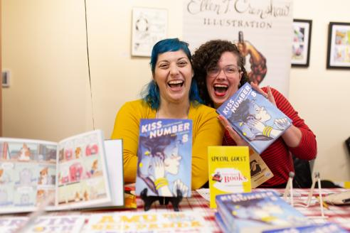 Photo of 2 women behind a table holding up comic books and smiling and laughing
