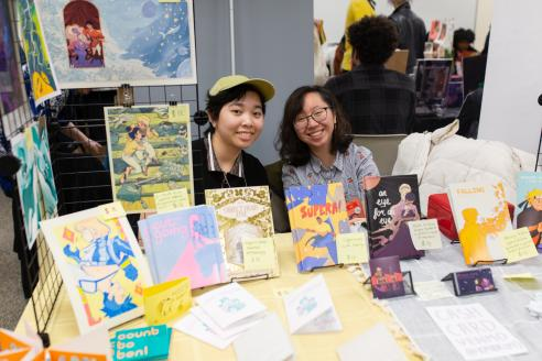 2 artists behind a table at a comic book convention with books and papers in front of them