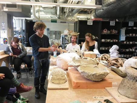 students sit around large studio table discussing clay sculpture work