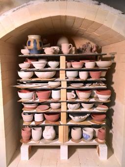 large gas kiln is filled with multiple shelves of ceramic dishes and vessels