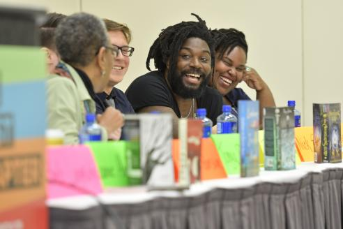 Jason Reynolds smiles as he sits on a panel with fellow authors.