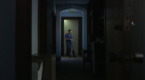 A person stands in a doorway in the distance of dark house
