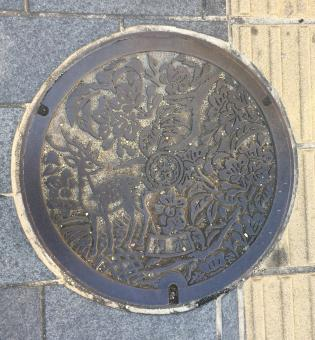 Manhole cover with flowers and a deer.