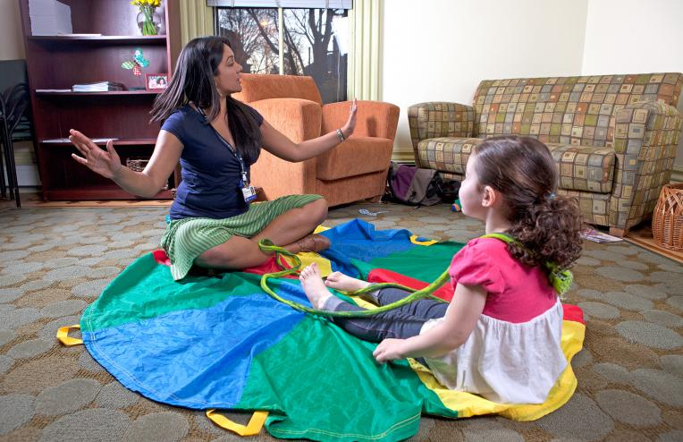 female expressive therapist sitting with small child on a parachute engaging her in play therapy