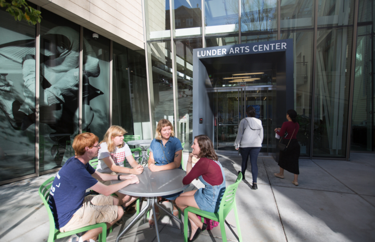 students sitting outside lunder arts center