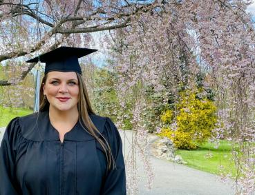 Alice Smith in graduation gown outside in front of blooming tree.