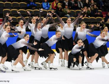 The Haydenettes - in costume on the ice. Hands out and smiling for group picture.