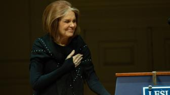 Gloria Steinem laying her hand across her chest in a gesture of gratitude
