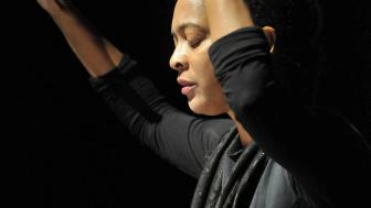 Danielle Legros Georges on a stage, eyes closed, hands up, performing.
