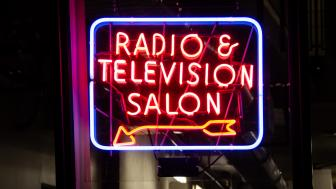 "Neon sign that reads: ""radio and television station"" with an arrow pointing to the bottom left corner of the rectangular sign."