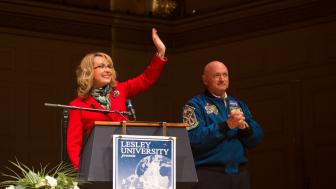 Gabby Giffords waves and Mark Kelly clasps his hands on stage.