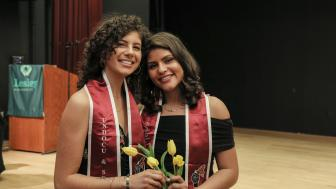 Jeannine Hernandez and Vita Franjul wearing the crimson stoles each graduate received