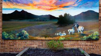 The mural on a brick wall - the image is a landscape with a herd of animals.