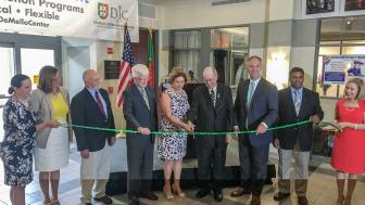 Leaders from Lesley and the Rising Tide partners stand in a line behind long ribbon being cut in the DeMello International Center.