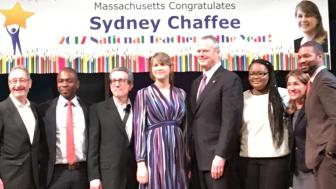 Sydney Chaffee stands on stage with Gov. Charlie Baker, colleagues and students at her ceremony. Behind her is a sign that reads Massachusetts Congratulates Sydney Chaffee.