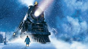 Image of boy in front of train in the snow.