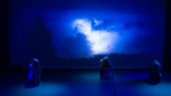 A photograph of the Marran Theater stage during a dress rehearsal of the Oxford Street Players porduction of Macbeth with three witches in front of a screen of blue clouds