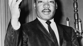 Martin Luther King Jr, black and white picture, has right hand raised.