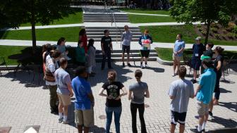 Students standing outside on the quad in a circle on a sunny summer day