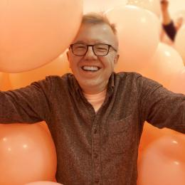 Headshot of Jim Hood surrounded by pink balloons