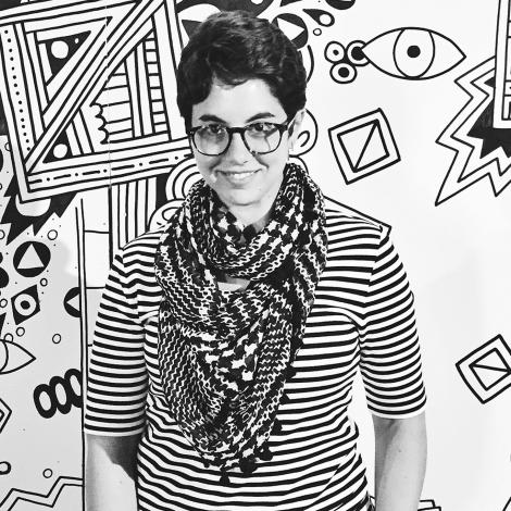 Black and white image of Kate Castelli standing in front of illustration of various lines and shapes